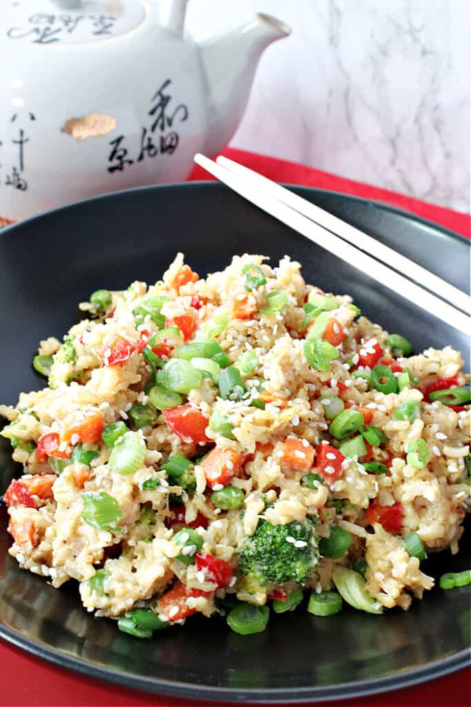 A vertical closeup image of Brown Rice Fried Rice with Vegetables and Eggs in a black bowl with chop sticks on the side.