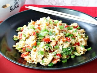 A black bowl of Brown Rice Fried Rice with Vegetables and Eggs sitting on a red plate with chop sticks on the side.