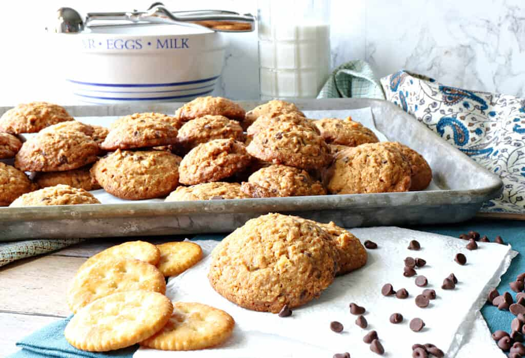 A horizontal photo of a full baking sheet with Butterscotch Ritz Cookies in the background and a few cookies with crackers and chocolate chips in the foreground.
