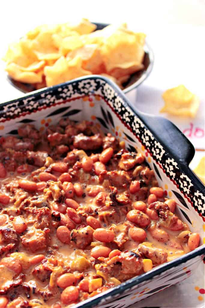 A closeup horizontal photo of a square baking dish filled with Cheesy Sausage Bean Dip and a bowl of chips in the background.