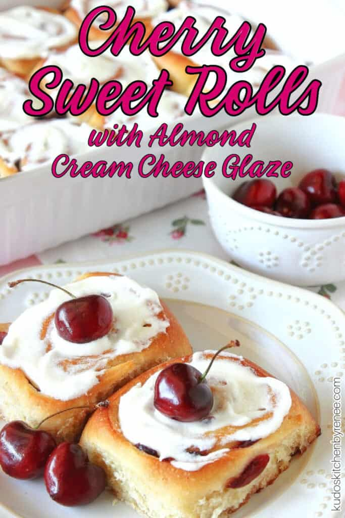 A vertical closeup photo of two Cherry Sweet Rolls on a plate with a small bowl of cherries in the background along with a title text overlay graphic.