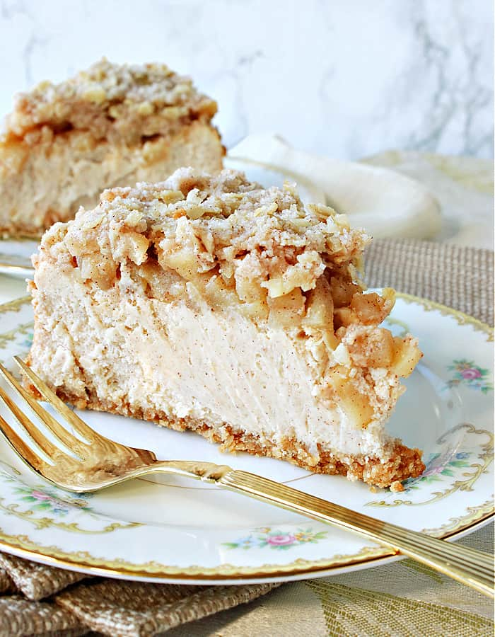 A creamy slice of Dutch Apple Cheesecake on a china plate with a gold fork in the forefront.