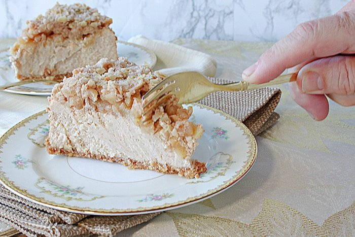 A hand holding a fork and digging into a slice of Dutch Apple Cheesecake on a pretty china plate.