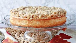 A whole Dutch Apple Cheesecake on a glass cake stand.