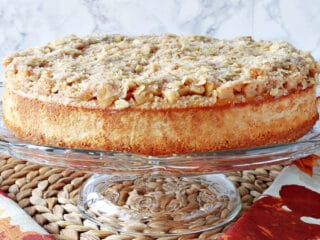 A whole Dutch Apple Cheesecake on a glass cake stand.