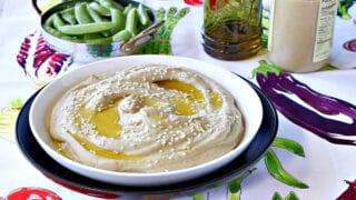 A white bowl filled with Eggplant and Chickpeas Hummus in the foreground and a small bowl of sugar snap peas in the background.
