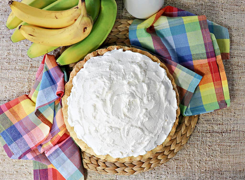 An overhead photo of an entire banana cream pie topped with whipped cream with fresh bananas in the background.