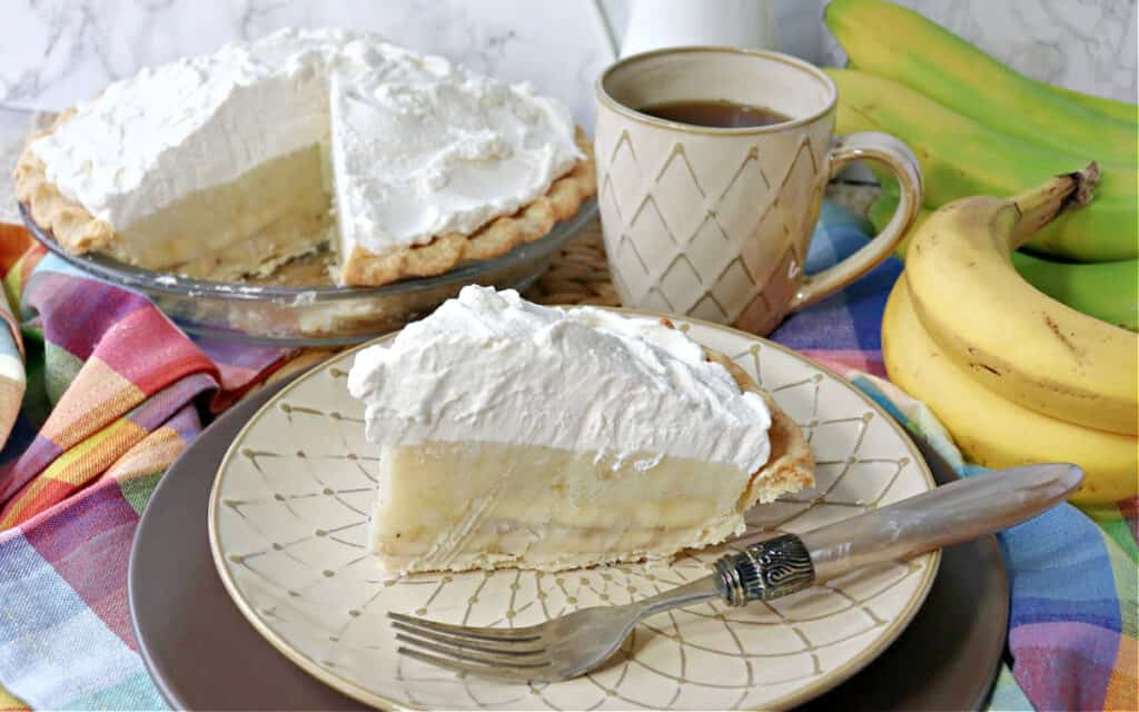 A slice of Mom's Best Banana Cream Pie on a plate with a fork along with a cup of coffee and the rest of the pie in the background.