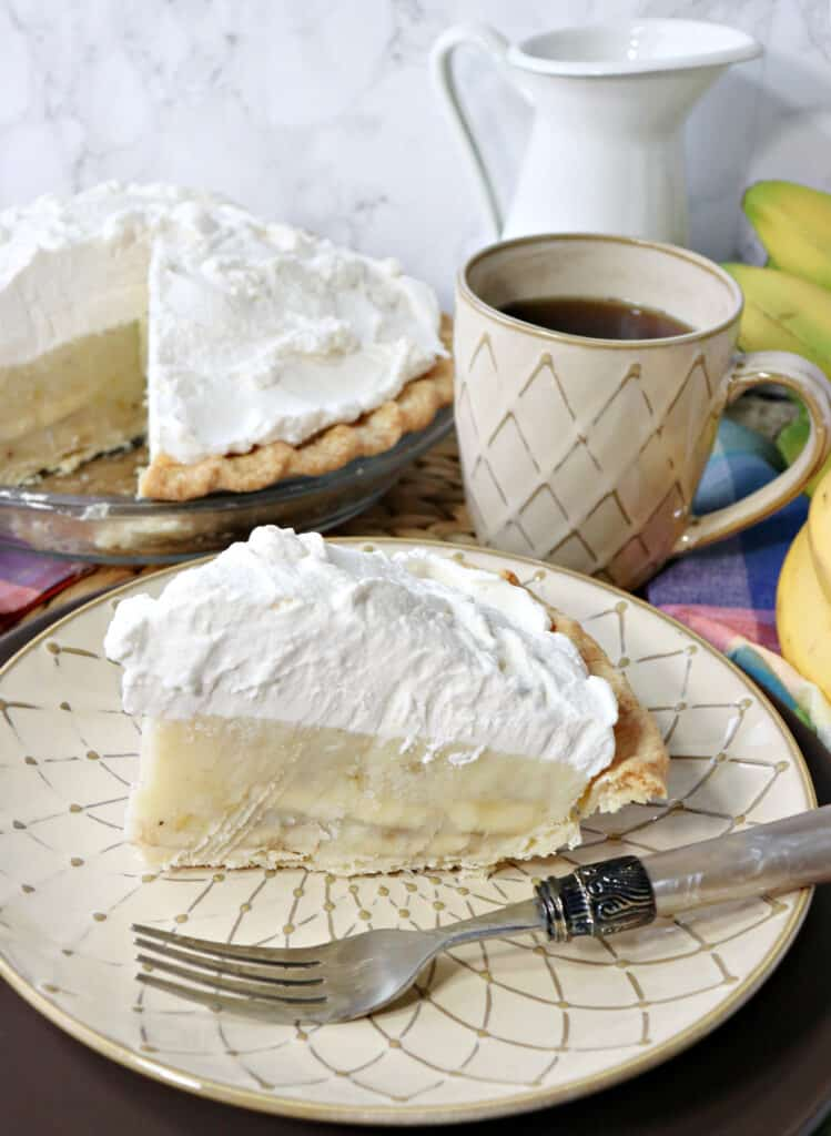 A slice of Mom's Best Banana Cream Pie on a plate with a fork with a cup of coffee and the rest of the pie in the background.