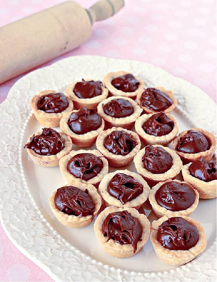 A pretty white platter filled with Nutella Cookie Cups on a pink polka dot tablecloth.