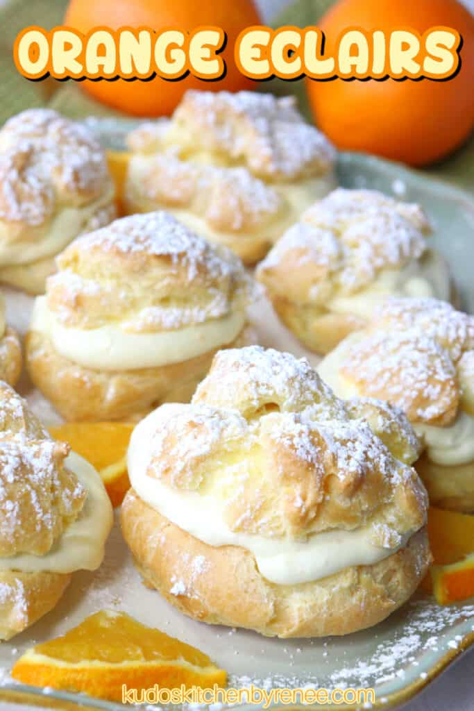 A vertical closeup of Orange Cream Eclairs on a plate topped with powdered sugar and some fresh orange slices on the plate.