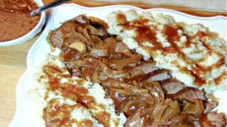 A Slow Cooker Beef Brisket on a white plate covered in gravy and onions.