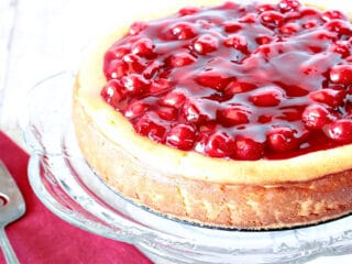 An offset horizontal photo of a Traditional Cherry Cheesecake on a glass cake stand with a cake server and a red napkin.
