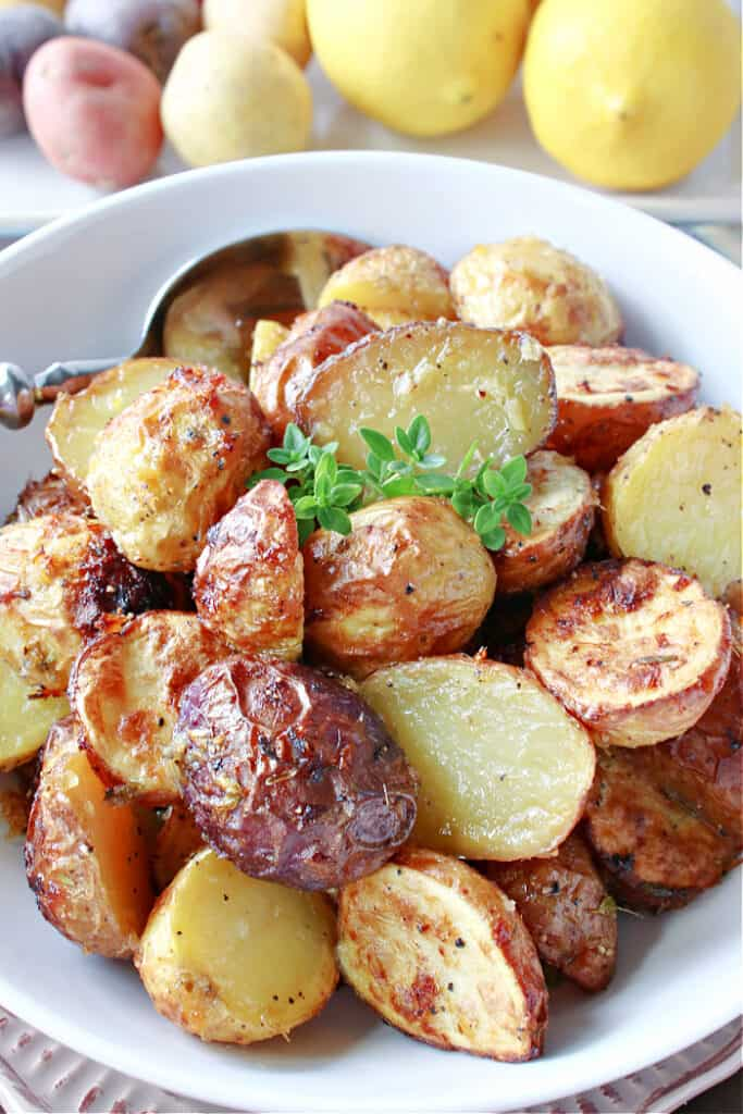 A closeup vertical image of golden brown Air Fryer Baby Potatoes in a white bowl with lemons and baby potatoes in the background.