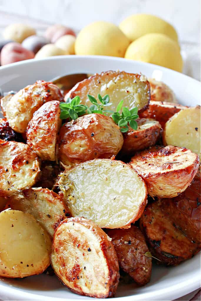 Super closeup vertical photo of golden and crispy Air Fryer Baby Potatoes along with some fresh thyme as garnish.
