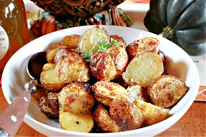 A closeup horizontal photo of a white bowl and a spoon along with golden Air Fryer Baby Potatoes and some fresh thyme as garnish.