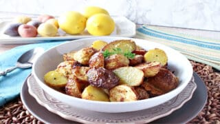 A horizontal photo of a white bowl filled with Air Fryer Baby Potatoes with fresh lemons and potatoes in the background.