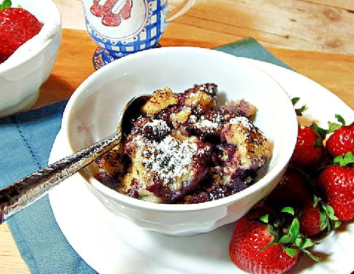 A small white bowl filled with Blueberry Grunt along with a spoon and some fresh strawberries.