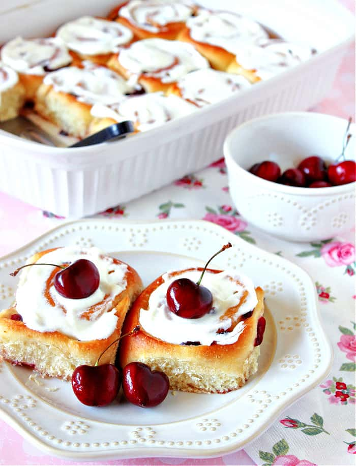 A vertical closeup photo of two Cherry Sweet Rolls on a white plate with cream cheese almond glaze and fresh cherries as garnish.