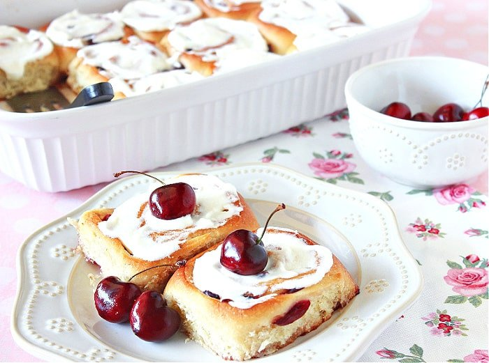Two Cherry Sweet Rolls on a white plate with a rose bud tablecloth and fresh cherries as garnish on the buns.