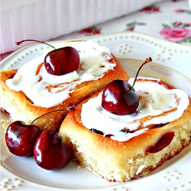 A square closeup photo of two Cherry Breakfast Buns on a white plate with fresh cherries as garnish.
