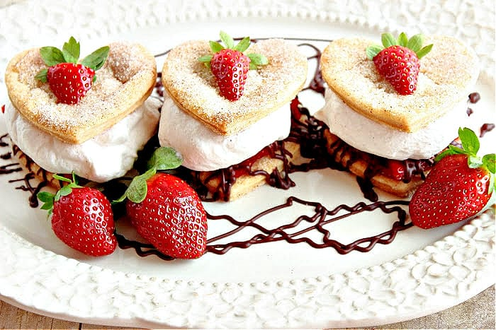Three Deconstructed Strawberry Pies on a pretty platter with chocolate ganache and fresh strawberries as garnish.