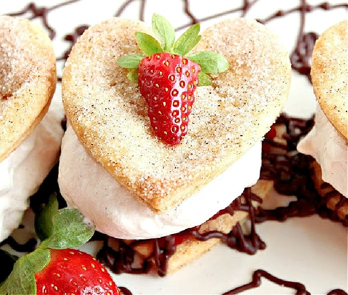 A super closeup of a Deconstructed Strawberry Pie with a cinnamon-sugar crust-pie heart along with fresh strawberries and chocolate ganache.