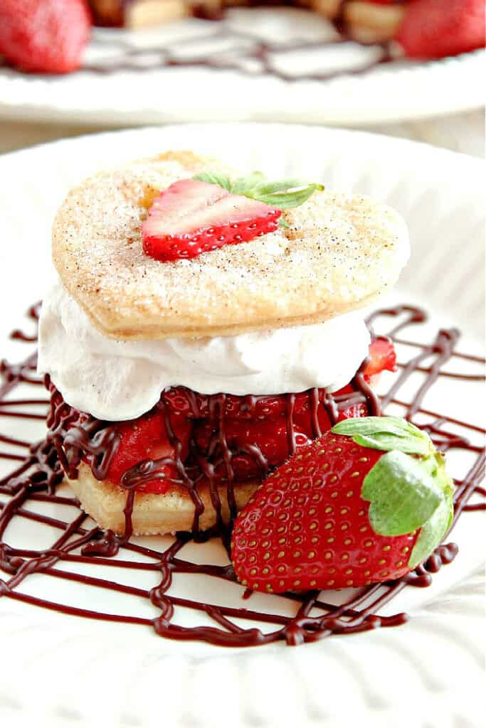 A closeup vertical image of a Deconstructed Strawberry Pie with cinnamon sugar pie crust hearts, strawberries, and chocolate ganache.