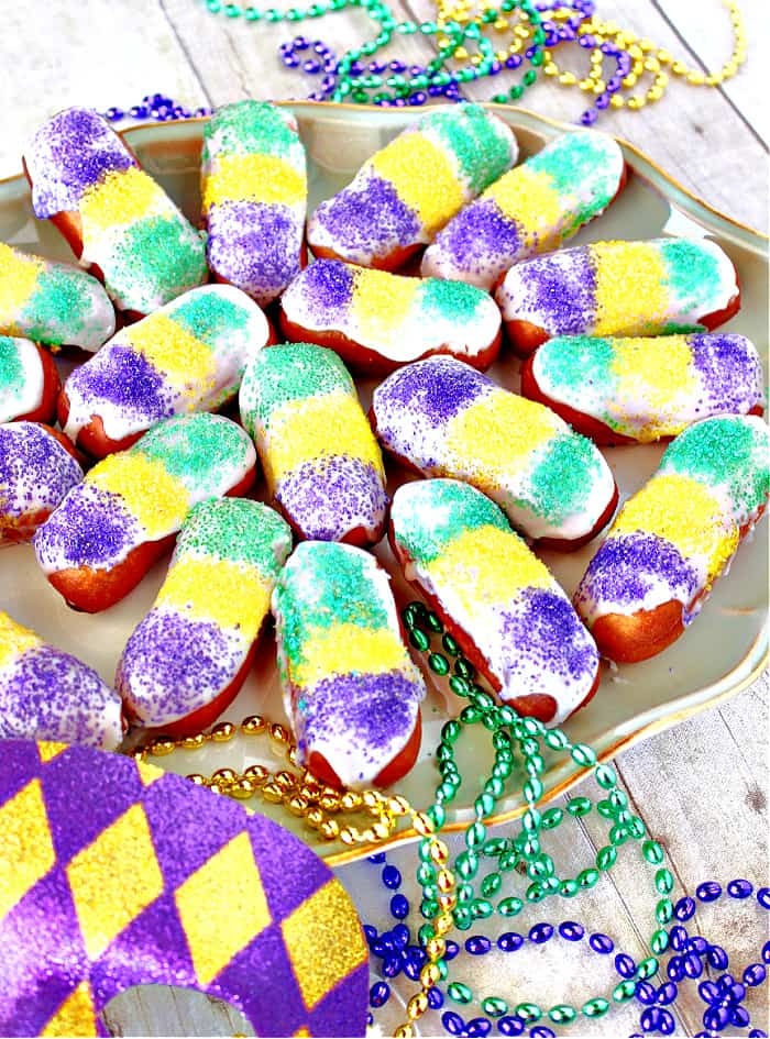 A vertical closeup image of a plate of Mini Long John with colorful sanding sugar and Mardi Gras beads.