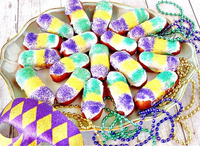 A platter filled with Mini Long Johns that have been decorated for Mardi Gras with green, yellow, and purple sanding sugar.