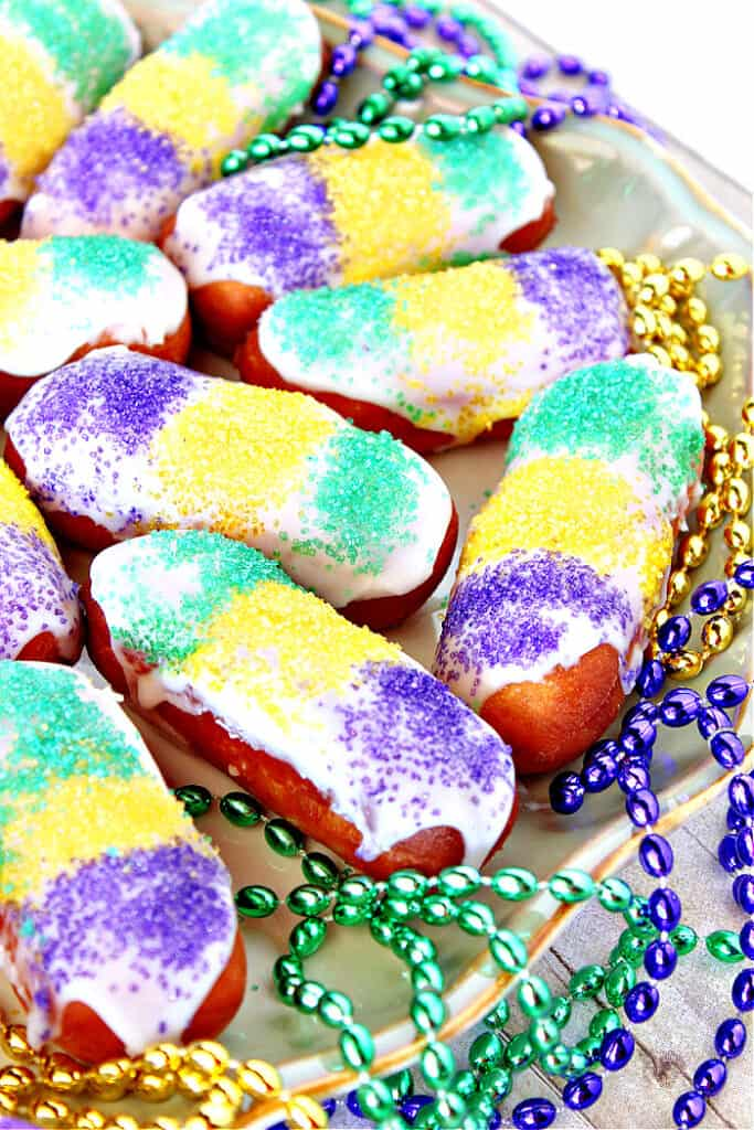 A vertical closeup of a plate of Mini Long Johns along with purple, green, and yellow sanding sugars.