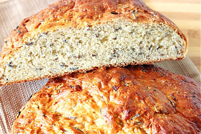 A closeup horizontal photo of a slice of Wild Rice Bread with onions with a golden crust.
