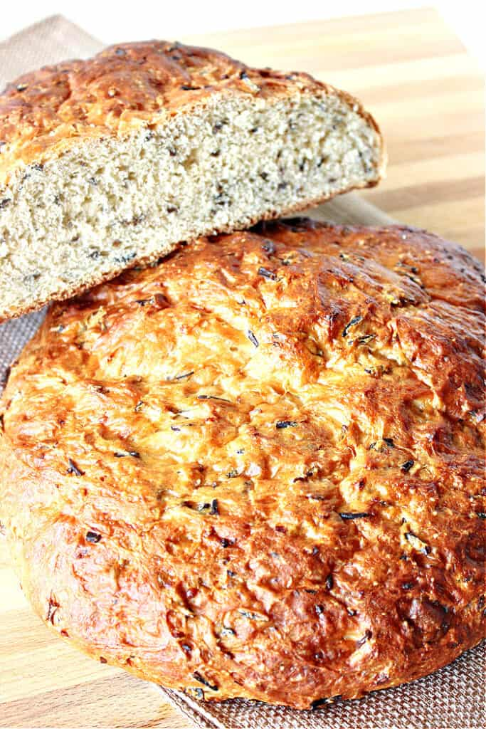 A vertical closeup of a golden rustic loaf of Wild Rice Bread with Onions along with a sliced loaf on top.