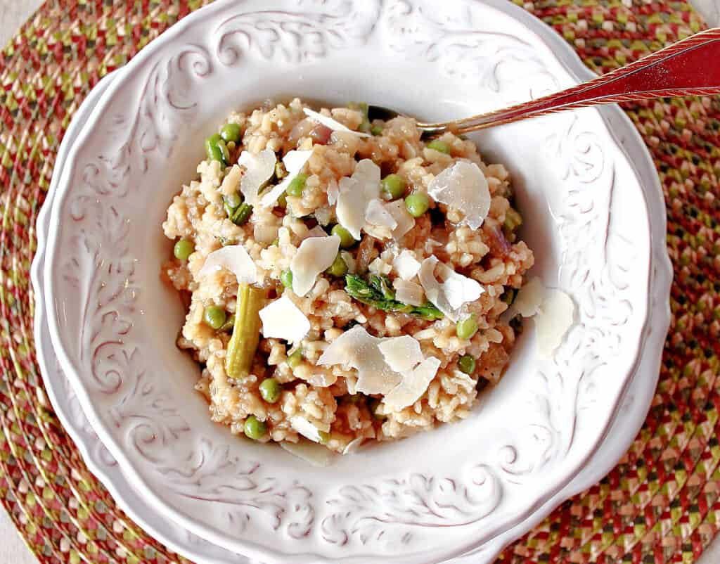 A direct overhead photo of a white bowl filled with Asparagus and Pea Risotto along with a spoon and a placemat.