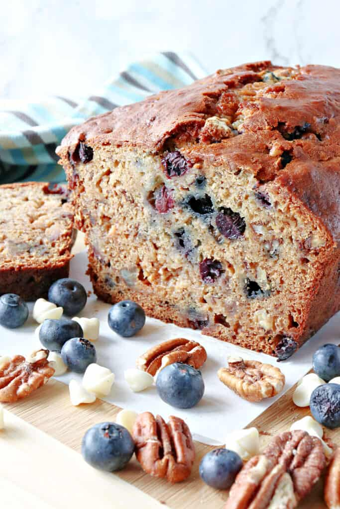 A vertical closeup of the inside of a Blueberry Banana Quick Bread which shows pecans, and blueberries inside.