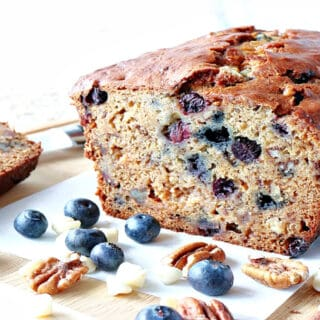 A sliced loaf of Blueberry Banana Quick Bread along with fresh blueberries, pecans, and white chocolate chips on the table.