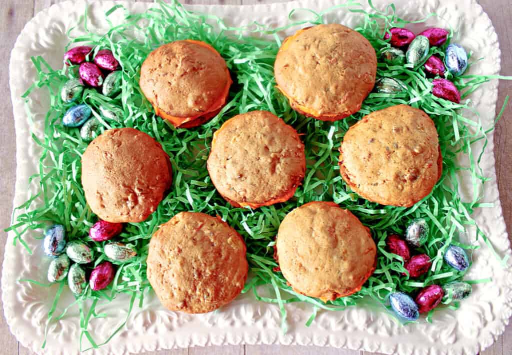 A directly overhead photo of a platter of Carrot Cake Whoopie Pies with green Easter grass and foil covered chocolate eggs.