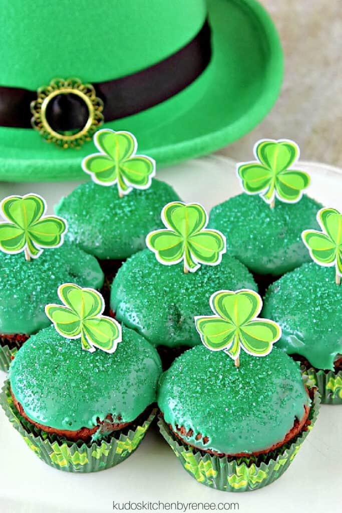 A vertical closeup photo of cute green Chocolate Mint Brownie Cupcakes with sanding sugar and paper shamrocks on top.