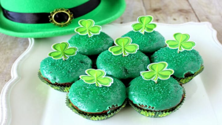 A white scalloped plate filled with Chocolate Mint Brownie Cupcakes with a green glaze and paper shamrocks on top.