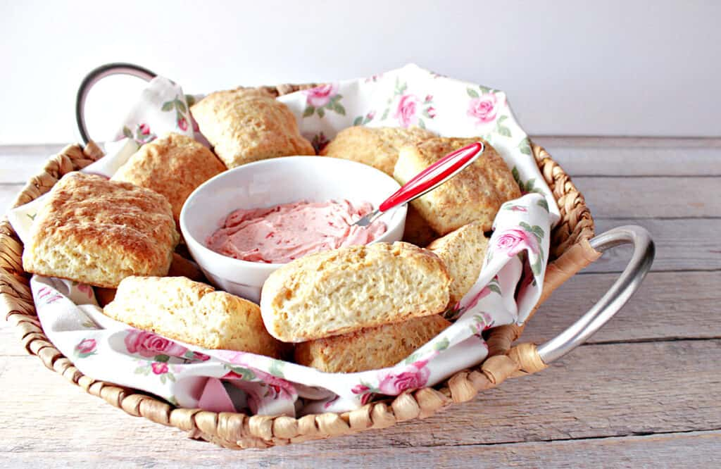 A pretty basket with silver handles filled with a pretty napkin along with Cream Cheese Biscuits and some strawberry butter.