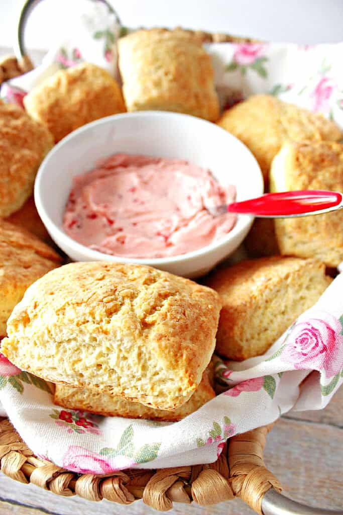 A vertical closeup of a basket of Cream Cheese Biscuits with a bowl of strawberry butter in the center.