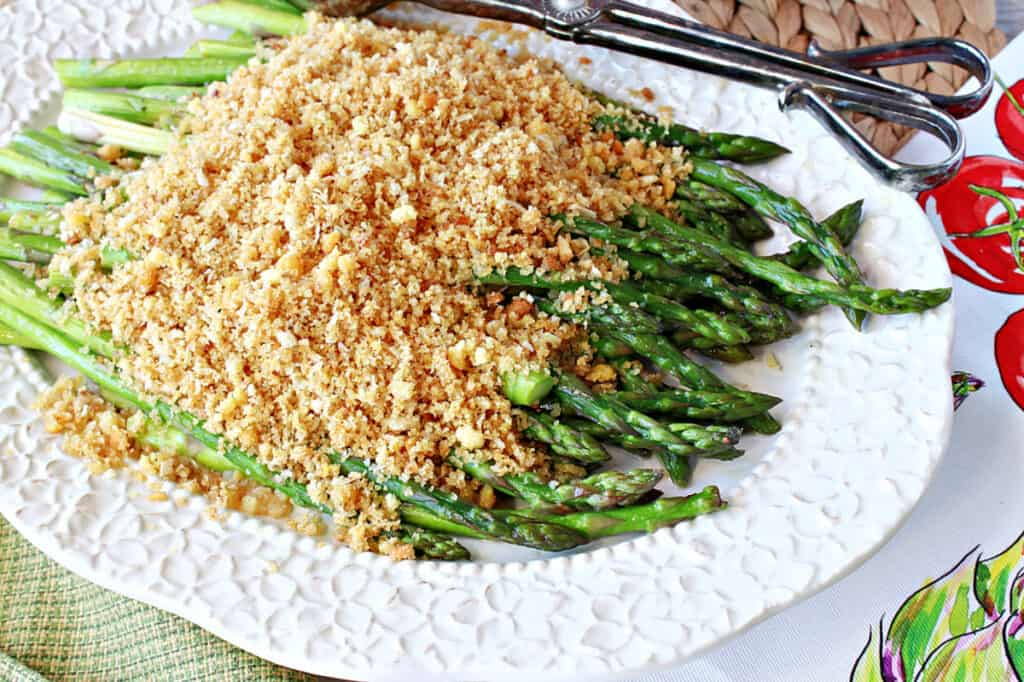 An offset horizontal photo of Asparagus with Breadcrumbs on a pretty white platter with a set of serving tongs on the side of the platter.