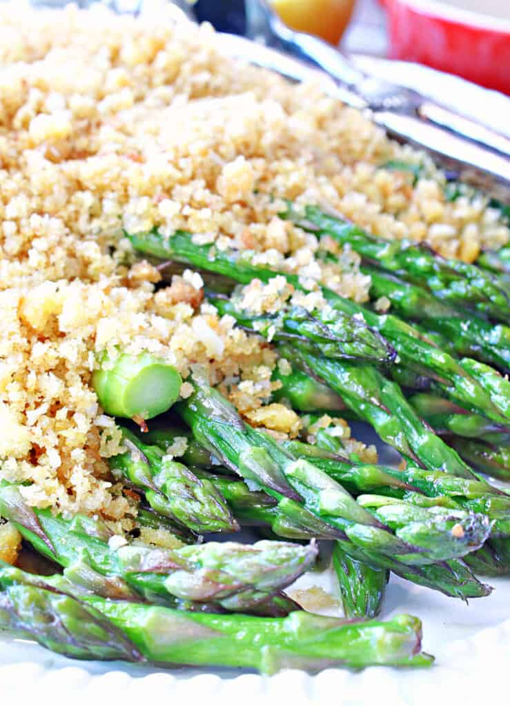 A super closeup vertical image of cooked asparagus on a platter covered in seasoned breadcrumbs.