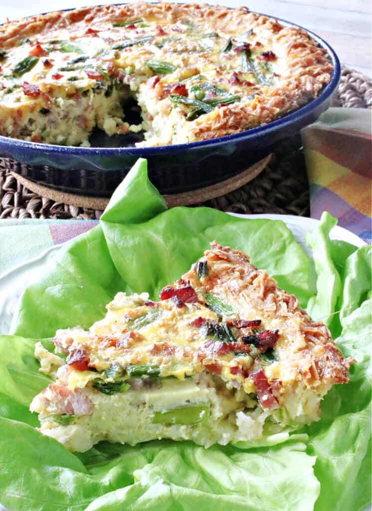 A vertical closeup of a slice of Ham and Asparagus Quiche in the foreground on top of lettuce and a whole quiche in the background.