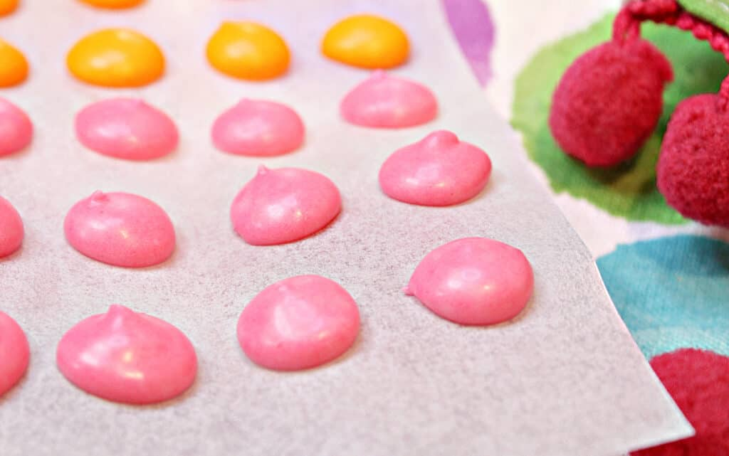 A super closeup horizontal image of pink Homemade Candy Dots on a strip of white parchment paper.