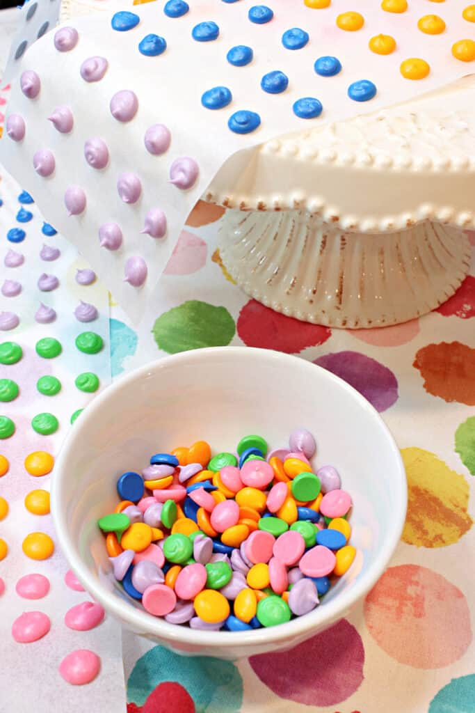 A vertical image of a small white bowl filled with bright colorful Homemade Candy Dots on a colorful polka dot napkin.
