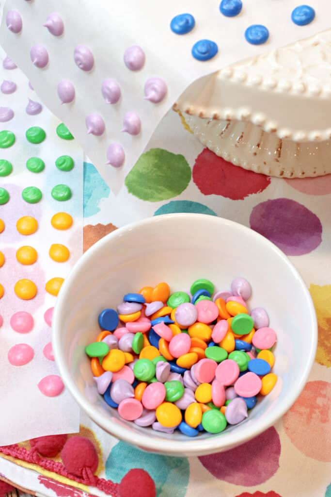 A vertical closeup of colorful homemade candy buttons in a bowl and also on paper strips in the background.
