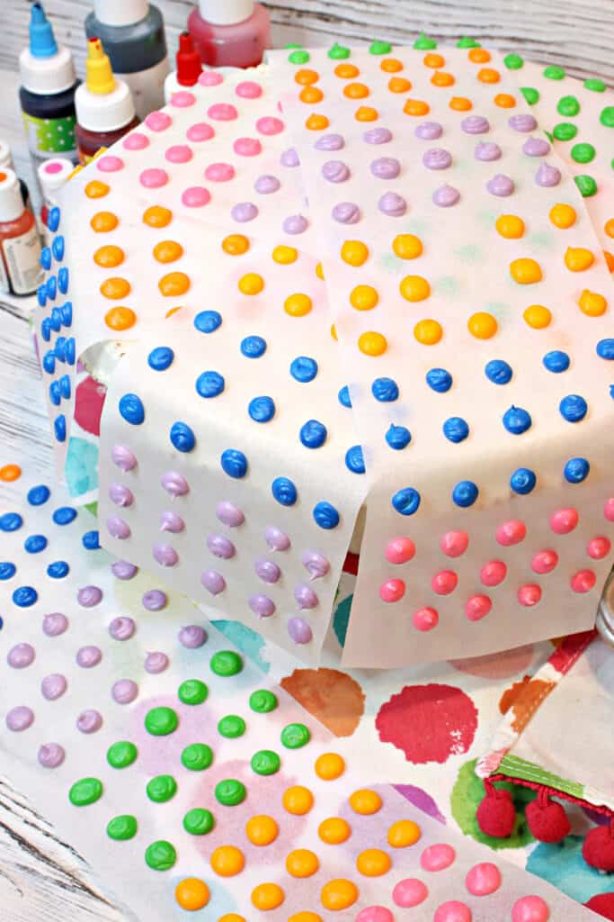 A vertical closeup of many strips of colorful Homemade Candy Dots with pink, green, purple, and yellow candy.