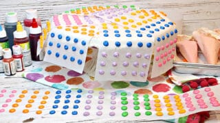 A cake plate and table filled with colorful Homemade Candy Dots on paper strips.
