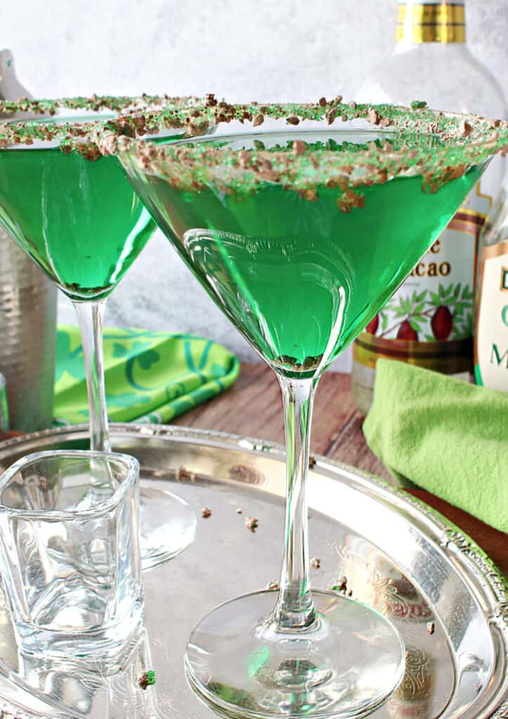 A close vertical image of two green Irish Grasshopper Cocktails on a silver platter.